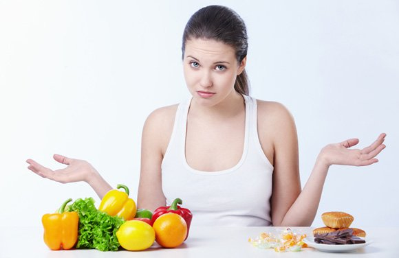 ผู้หญิงกับผลไม้และอาหารขยะบนโต๊ะ