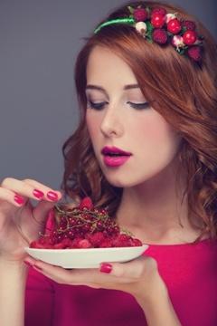 ผู้หญิงผมแดงกำลังกินผลเบอร์รี่