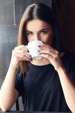 หนุ่มสาวผมสีน้ำตาลกำลังดื่มกาแฟ