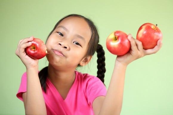 เด็กสาวถือแอปเปิ้ลสามลูก