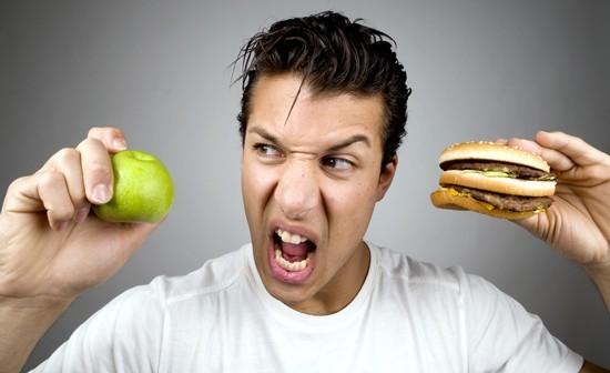 ชายหนุ่มถือแอปเปิ้ลและแฮมเบอร์เกอร์