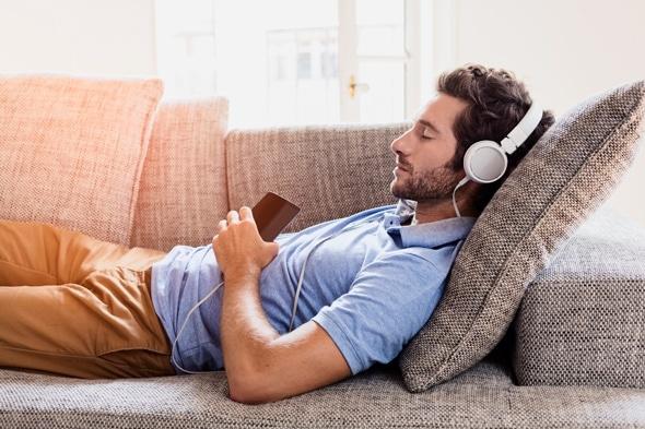 ชายหนุ่มนอนอยู่บนโซฟาฟังเพลง