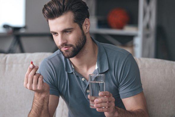 ชายหนุ่มถือยาและแก้วน้ำในมือ
