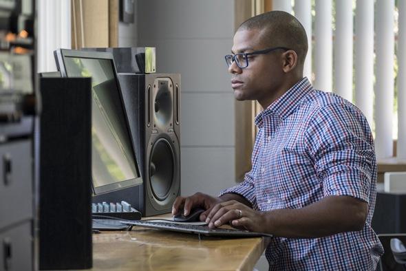 ชายหนุ่มมืออาชีพยืนทำงานที่คอมพิวเตอร์