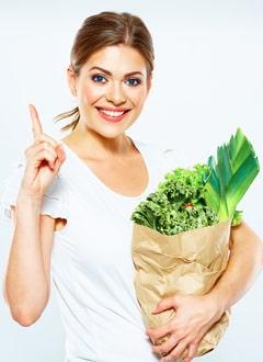 หญิงสาวถือถุงกระดาษพร้อมผัก