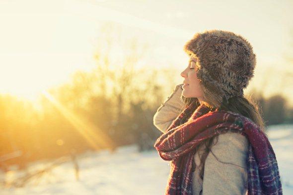 หญิงสาวข้างนอกในวันที่อากาศหนาวเย็นหันหน้าเข้าหาดวงอาทิตย์